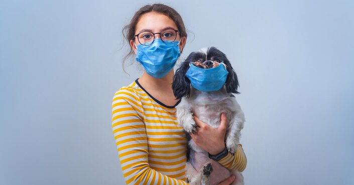 A girl holding a dog both wearing face masks