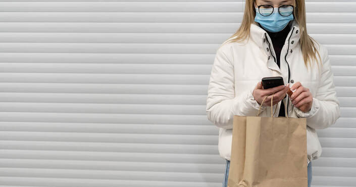A woman wearing a face mask is making an online payment via mobile phone