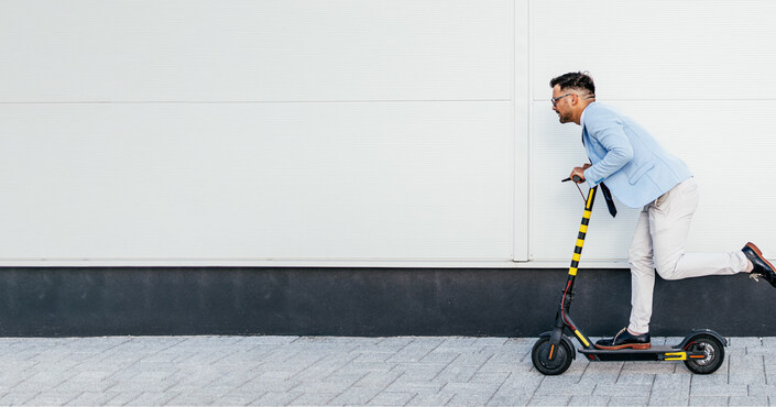 Illustration of mobility industry rise where a business casual man is riding a scooter